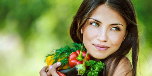 a model is hugging a variety of vegetables and holding them close to her chest. she is grinning and looking to the right