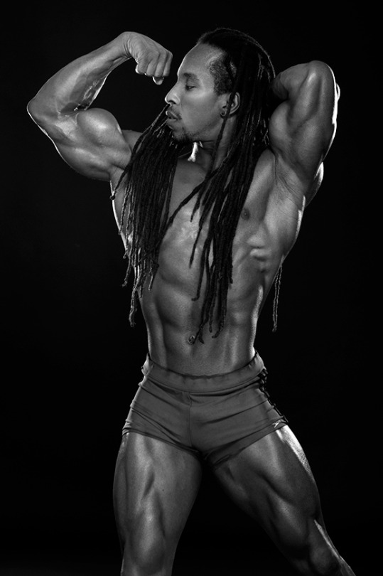 A B&W photo of vegan body builder, Torre Washington who is flexing their muscles for the camera