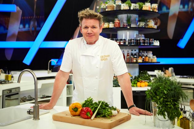 Gordon Ramsay leaning over a cutting board full of vegetables